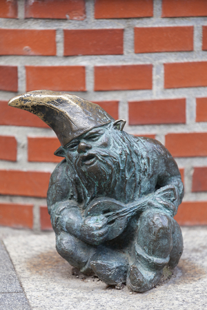 WROCLAW - POLAND, JUNE 12, 2017 : Wroclaw dwarf, small fairy-tale bronze figurine on the side walk, musician, Wroclaw, Poland. There are over 350 dwarfs spread all over the city, they are a big tourist attraction