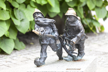 Wroclaw dwarf, small fairy-tale bronze figurine on the side walk, firefighters. There are over 350 dwarfs spread all over the city, they are a big tourist attraction