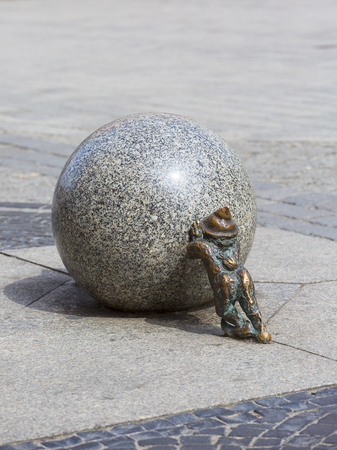 WROCLAW - POLAND, APRIL 14, 2018 : Wroclaw dwarf, small fairy-tale bronze figurine on the side walk,  Wroclaw, Poland. There are over 350 dwarfs spread all over the city, they are a big tourist attraction Editorial