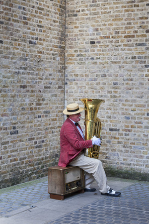 LONDON, UNITED KINGDOM - JUNE 22, 2017: Elegant man playing the tuba on the street for money