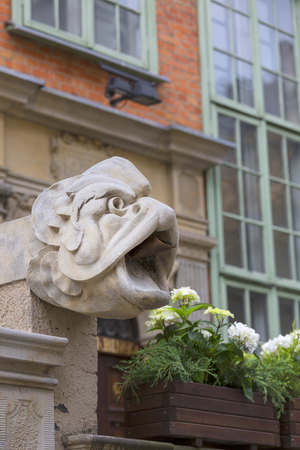Mariacka street, grotesque gargoyle on front of colorful tenement house, Main city, Gdansk, Poland