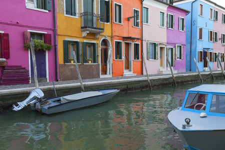 Colorful small, brightly painted houses on the island of Burano, reflection in the water. Burano is an island in the Venetian Lagoon, situated 7 kilometers  from Venice Stock Photo