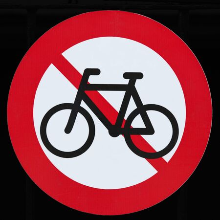 Prohibition sign for bicycles, white-red on a black background, close up
