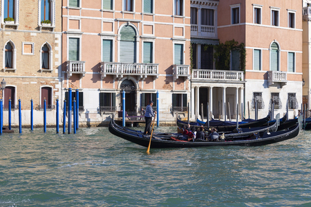VENICE, ITALY-SEPTEMBER 21, 2017: Venetian gondolier rowing through the Grand Canal. Gondola is iconic traditional boat, very popular means of transport for tourists