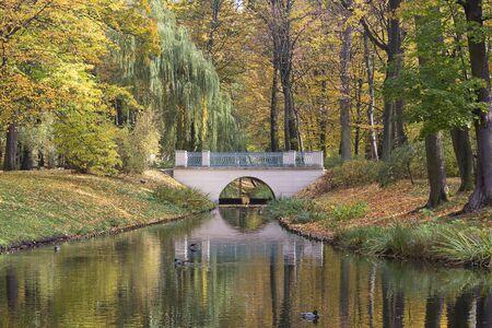Picturesque and charming garden park in autumn colors, bridge over water, Royal Baths Park, Lazienki Warszawskie, Warsaw, Poland