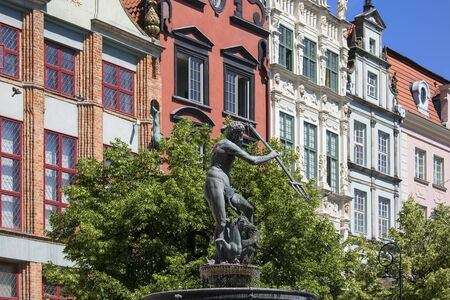GDANSK, POLAND - JUNE 6, 2018: 17th century Neptune's Fountain Statue at Long Market Street by the entrance to Artus Court, colorful tenement houses