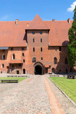 Malbork, Poland - June 25, 2020: 13th century Malbork Castle, medieval Teutonic fortress on the Nogat River.  It is the largest castle in the world, UNESCO World Heritage Site