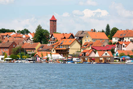 Mikolajki, Masuria, Poland - June 24, 2020: View from Mikołajskie Lake of town, marina for yachts and boats at the waterfront. Mikolajki is called the sailing capital of Poland