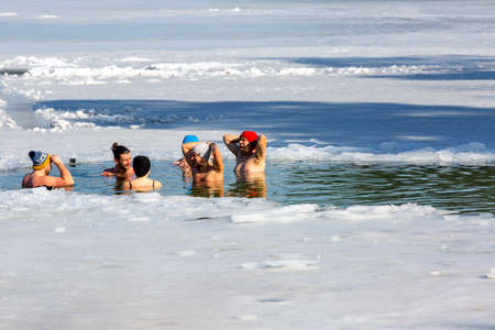 Krakow, Poland - February 20, 2021: Group of people submerged in cold water while winter swimming in an ice hole of a frozen Kryspinow lake Redakční