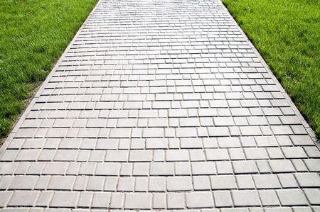 sidewalk between green grass photo