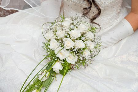 white fine rose in wedding bouquet in hand photo
