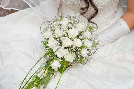 white fine rose in wedding bouquet in hand