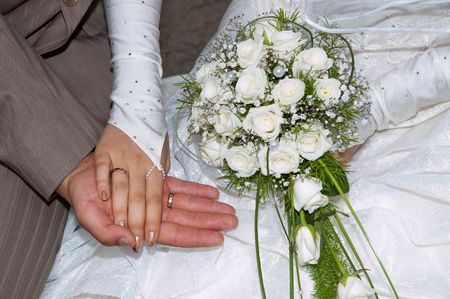 arm bouquet: two hands close up just merried with rings Stock Photo