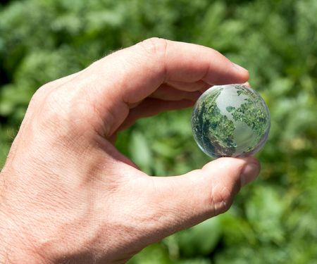 world in hand over green photo