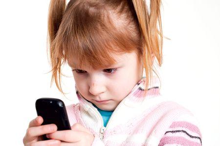 little girl looks on mobile phone photo