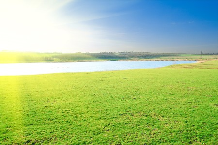 sun over pond and green grass photo