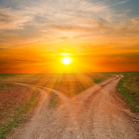 dirt road: two dirty ways under sunrays. sunset time Stock Photo