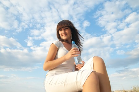young woman with bottle of water outdoors photo