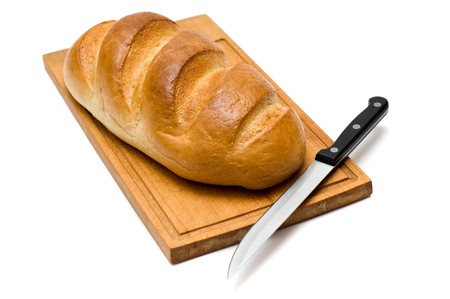 fresh natural bread with knife on breadboard photo