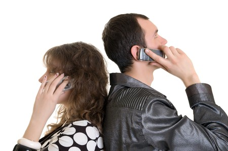ear phones: boy and girl talking by cell phone Stock Photo