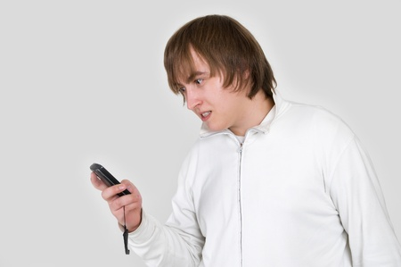 portrait of a unhappy young man with the phone in hand photo