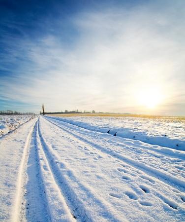 january sunrise: camino rural bajo la nieve. puesta de sol de invierno Foto de archivo
