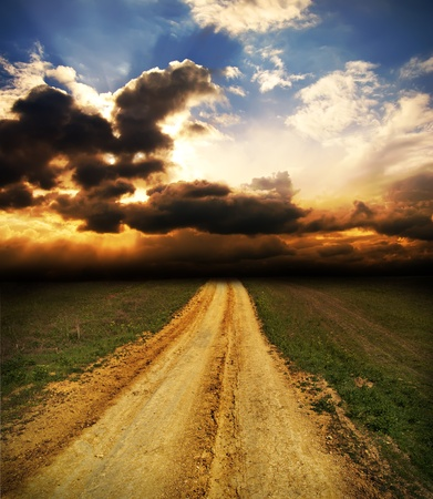 cloudy sunset over dirty road photo