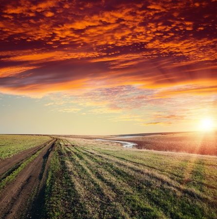 red sunset over river and rural road with dramatic sky Stock Photo - 9086291