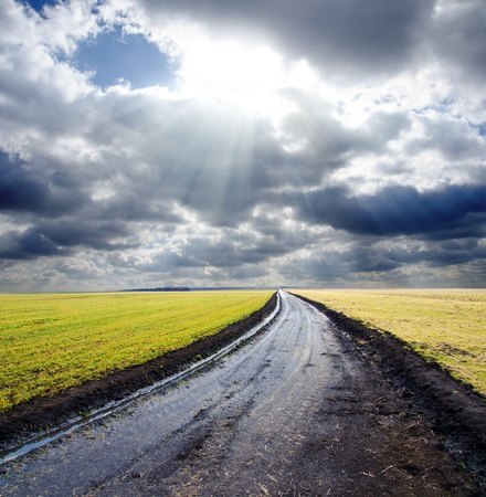 wet rural road under dramatic cloudy sky with sunbeams Stock Photo - 9086292