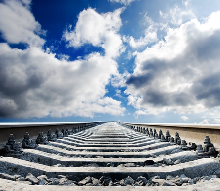 rail track: railway to horizon under cloudy sky Stock Photo