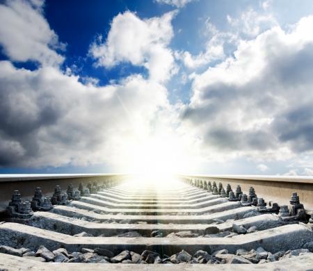 ferrocarril al sol bajo cielo nublado