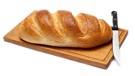 fresh bread with knife on breadboard photo