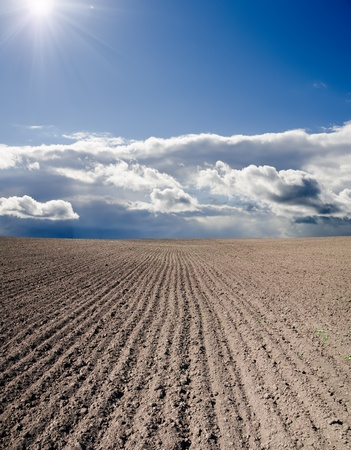 ploughed: black ploughed field under blue cloudy sky with sun