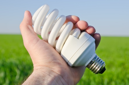 energy saving lamp in hand over green field photo