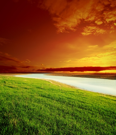 red sky on sunset over river and green grass photo