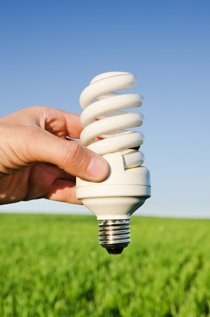 energy saving lamp in hand over green field Stock Photo - 9470487