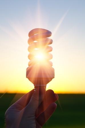 ahorro energia: ahorro de energ�a l�mpara en rayo de sol en la puesta de sol