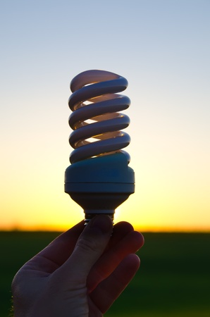 energy saving lamp in hand over sunset Stock Photo - 9590086