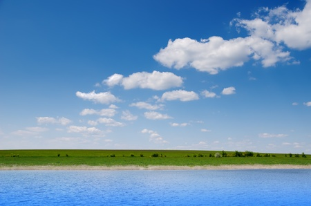 water and green field under deep blue cloudy sky Stock Photo - 9623544