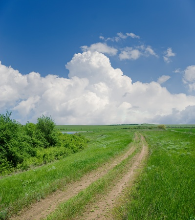 dirt road: rural road under clouds Stock Photo