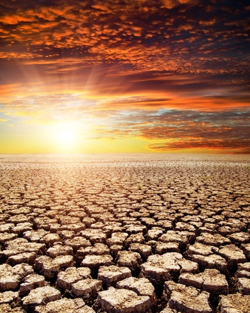 Tierra de sequía en la puesta de sol rojo