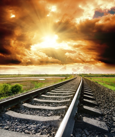 sun track: railway to cloudy sky at sunset Stock Photo