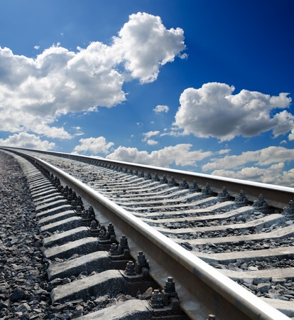 rail: low view to railroad under deep blue cloudy sky Stock Photo