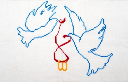 lovebird: Embroidered good by cross-stitch pattern. White doves holding wedding rings