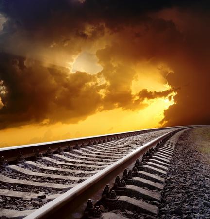 劇的な空の下で地平線への鉄道