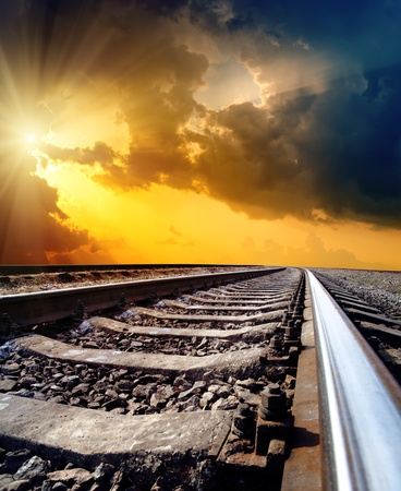 railroad track: railway to horizon under dramatic sky with sun