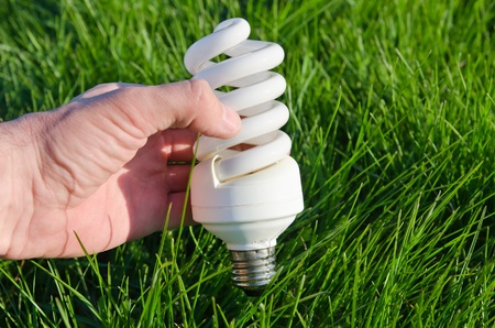 energy saving lamp in hand over green grass photo