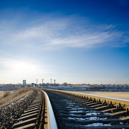 railroad to horizon under deep blue sky in sunset photo