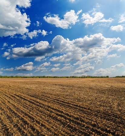black ploughed field under deep blue sky with clouds photo