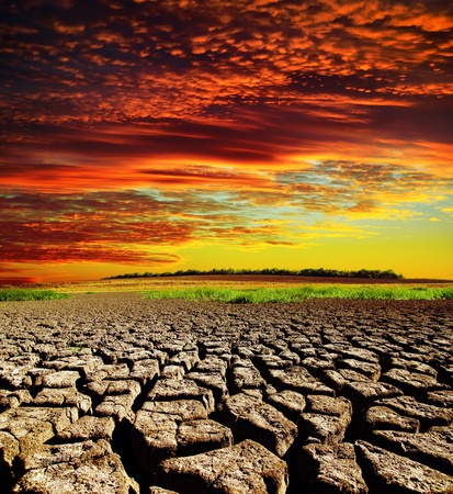 cracked earth: red dramatic sunset over dry cracked earth